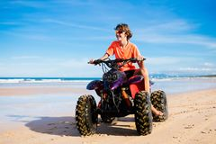 Teenager riding quad bike on beach. Teenager riding quad bike on tropical beach. Active teen age boy on quadricycle. All-terrain vehicle ride. Motor cross sports Royalty Free Stock Photos