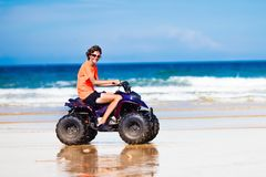 Teenager riding quad bike on beach. Teenager riding quad bike on tropical beach. Active teen age boy on quadricycle. All-terrain vehicle ride. Motor cross sports Stock Photo