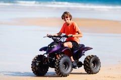 Teenager riding quad bike on beach. Teenager riding quad bike on tropical beach. Active teen age boy on quadricycle. All-terrain vehicle ride. Motor cross sports Royalty Free Stock Photo