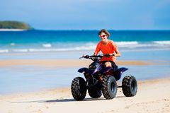 Teenager riding quad bike on beach. Teenager riding quad bike on tropical beach. Active teen age boy on quadricycle. All-terrain vehicle ride. Motor cross sports Royalty Free Stock Image