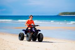 Teenager riding quad bike on beach. Teenager riding quad bike on tropical beach. Active teen age boy on quadricycle. All-terrain vehicle ride. Motor cross sports Stock Images