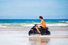 Teenager riding quad bike on beach. Teenager riding quad bike on tropical beach. Active teen age boy on quadricycle. All-terrain vehicle ride. Motor cross sports Stock Photography