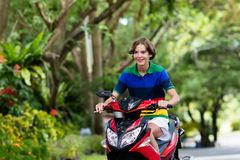 Teenager riding scooter. Boy on motorcycle. Teenager riding scooter. Teenage boy fun on motorbike ride on his way to school. Student on motorcycle in tropical stock photos