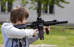 Teenager with rifle. Teenager aiming with automatic rifle Royalty Free Stock Photography