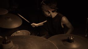 Teenager rock band drummer . cool and talented Asian American mixed young boy playing drums in headband performing song. In dark background feeling super star stock video