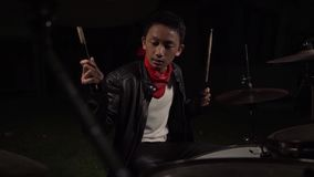 Teenager rock band drummer . cool and talented Asian American mixed young boy playing drums in leather jacket performing song. In dark background feeling super stock video