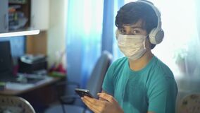A teenager in the room with headphones listening to music and looking at the phone under quarantine for self-isolation