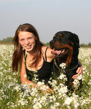 Teenager and rottweiler. Young woman sitting and her purebreed rottweiler dog Royalty Free Stock Photo