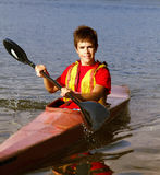 Teenager Rowing a Boat. Teenager enjoying the outdoors rowing a boat on a river Royalty Free Stock Image