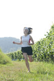 Teenager running in country. Happy young teenager in shorts running past vineyard in countryside Royalty Free Stock Photos
