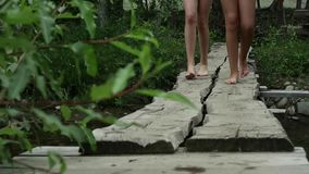 Teenager`s legs walking along a narrow wooden bridge over a mountain river. camping and adventure concept.  stock footage