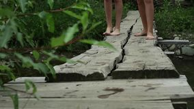 Teenager`s legs walking along a narrow wooden bridge over a mountain river. camping and adventure concept.  stock video