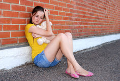Teenager's problems. Sad teenager girl with teddy bear sitting near brick wall Stock Images