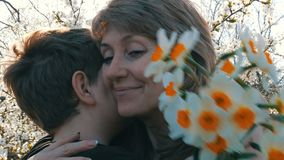 A teenager`s son presents an adult middle-aged mom a bouquet of white daffodils on the background of a blossoming tree