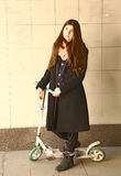 Teenager sad girl with long brown hair and black coat on scooter Royalty Free Stock Photos