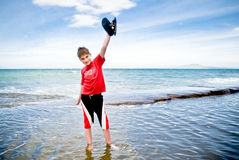 Teenager saluting with his sandals Royalty Free Stock Image