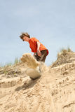 Teenager sandboarding down a dune Stock Images