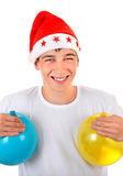 Teenager in Santa Hat. Happy Teenager with Two Balloons in Santa`s Hat On The White Background Royalty Free Stock Image