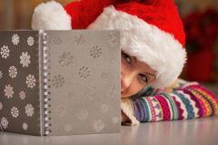 Teenager in santa hat looking out from notepad Stock Photos