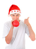 Teenager in Santa Hat. Teenager in Santa's Hat inflate Red Balloon and Pointing up Isolated On The White Background Royalty Free Stock Photography