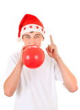Teenager in Santas Hat. Teenager in Santa's Hat inflate Red Balloon and Pointing up Isolated On The White Background Stock Image