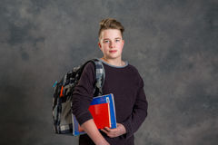 Teenager with satchel and books. In front of gray background Stock Photography
