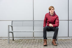 Teenager saw something interesting that caught his attention whi. Bored teen boy waiting sitting on bench saw something interesting that catched his attention Royalty Free Stock Images