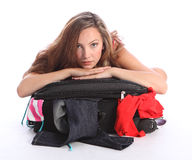 Teenager school girl fed up packing holiday case. Beautiful young teenager school girl leaning on top of suitcase looking fed up and tired of packing for her royalty free stock photography