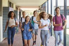 Teenager school kids running in high school hallway Royalty Free Stock Photo