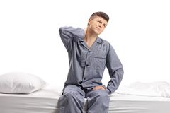 Teenager seated on a bed experiencing neck pain Royalty Free Stock Images