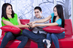 Teenager seizing a remote control. Three asian teenager sitting on sofa and fighting to take a remote control with winter background on the window Stock Photography