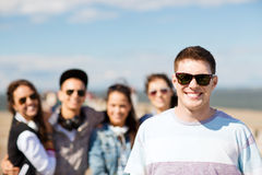 Teenager in shades outside with friends Royalty Free Stock Image