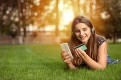 Teenager shooping online on phone using credit card stock photos
