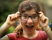 Teenager shortsighted girl with myopia wearing new sight correction glasses. Happy teenager shortsighted girl with myopia wearing new sight correction glasses royalty free stock images