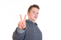 Teenager showing victory sign. Teenager in front of white background showing victory sign Royalty Free Stock Image