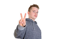 Teenager showing victory sign. Teenager in front of white background showing victory sign Royalty Free Stock Photo