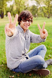 Teenager showing victory sign in park Royalty Free Stock Photography