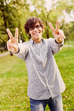 Teenager showing victory sign in park Stock Photo