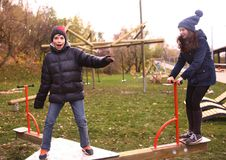 Teenager siblings boy and girl in warm clothes having fun in autumn park Royalty Free Stock Images
