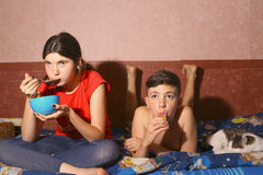 Teenager siblings brother and sister lay on sofa with cat. Eating dinner after school Stock Photography