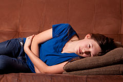 Teenager sick on couch. Young teenage girl holding stomach with an illness lying on a couch Stock Photography