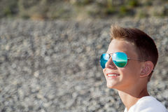 The teenager sits on the beach in blue glasses from the sun, the Stock Images