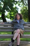 Teenager sits on bench and relaxes Stock Photos