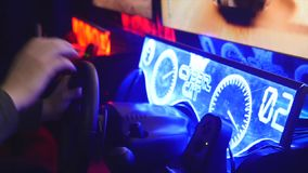Teenager sits and spins the wheel on the slot machine simulator races.  stock video