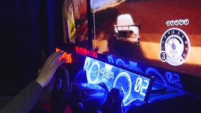 Teenager sits and spins the wheel on the slot machine simulator races.  stock video footage