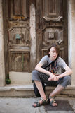A teenager. Sits on the threshold of a dilapidated house near an old front door Stock Photo