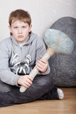 Teenager sits with unkind face with stone ax Stock Photography