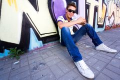 Teenager sitting against graffiti wall. Young man sitting against graffiti wall Royalty Free Stock Images