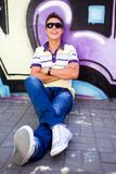 Teenager sitting against graffiti wall Royalty Free Stock Image