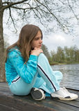 Teenager sitting alone near the lake Stock Photos